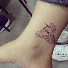 Tatuaje de la cabeza de una jirafa situado en el interior del...