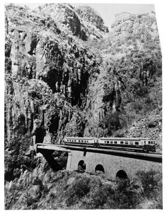 "Chihuahua - Pacific Railway's ""Autovias"" train, consisting of fiat diesel cars coming out of one of the 73 tunnels which are located on the line between La Junta and El Fuerte, Mexico on the 281 mile portion of the route traversing the mountain region over the Continental Divide around 1968."