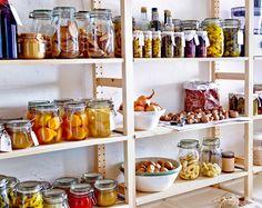 Três estantes de madeira IKEA com frascos, recipientes e garrafas com conservas e alimentos secos.