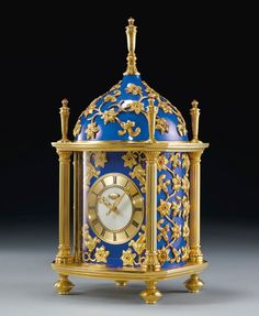PATEK PHILIPPE 'CONSTELLÉE BLEU DOME CLOCK'  -- magnificent yellow gold, ruby, mother-of-pearl & blue enamel dome mantel clock made in 1987.  Finely turned dial, outer gold chapter ring with Roman numerals.  Applied gold swathing floral motifs inset with cabochon rubies.