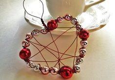 wire art heart with red and silver beads.