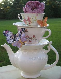 Planning a tea party themed event? Looking for the perfect gift for a friend who is a tea lover? This stacked teapot and teacup centerpiece is both unique and elegant.  With this centerpiece, you will receive a solid white or off-white teapot as the base, with two patterned teacups and two patterned saucers - all mismatched. They will be stacked, and glued permanently at a slight angle. Beautiful butterflies dot the centerpiece, with a single flower at the top to create a romantic feel…