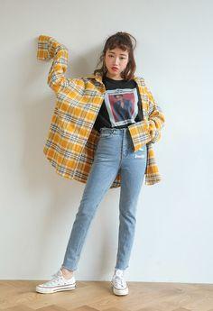 Elle porte une chemise à carreaux jaune avec des jeans et converse