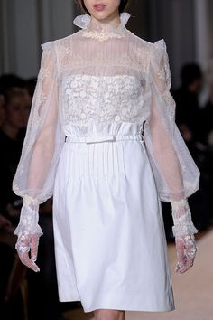 Ethereal antique-look white (organza?) sheer blouse. Pleated ruffle stand neckline, full bishop sleeves, and tea-stain lace appliques. Paired with an unspectacular paper-bag waist skirt. Valentino Couture Spring 2012.