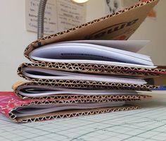 """Nossos livros cartoneros antes de passar pela """"prensa"""" que nada mais é do que colocar um peso em cima deles para que as capas fiquem assentadas. Eles ficam bem certinhos e nós adoramos receber o retorno das nossas leitoras surpresas com o toque no papelão e com a firmeza da costura e do acabamento dos livros. O papelão é um material surpreendente e ainda pode ser bastante experimentado em muitas artes já tem gente fazendo coisas incríveis com papelão há muito tempo peças realmente…"""