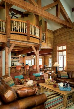 The great room presents an awe-inspiring display of log and timber. The log walls and elaborate trusses form an inviting backdrop to the home's open design, which encourages family and friends to interact.