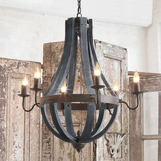 Wooden Wine Barrel Stave Chandelier Inspired by wooden slats from the vineyard, this bent-wood wine barrel chandelier is strapped with a dark bronze metal ring and 6 candelabra arms in rustic simplicity. Naturally aged wood finishes include Dark or Light Farmhouse Chandelier, Farmhouse Lighting, Rustic Lighting, Chandelier Shades, Chandelier Lighting, Iron Chandeliers, Wooden Chandelier, Foyer Chandelier, Modern Rustic Chandelier
