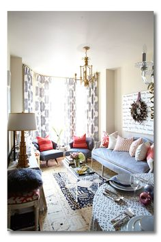 Ideas for Small Living Spaces. Longer settee, two armless curvy-backed chairs, and two stools around the fabric-draped tv table. Round dining table (without chairs) in the foreground. Two acrylic end tables create a clear coffee table on a neutral & navy rug.