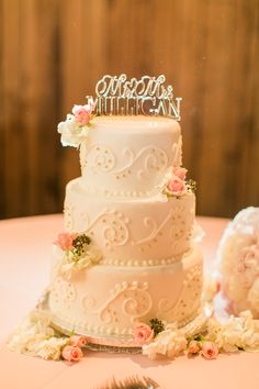 White Wedding Cake With Piping and Pink Flowers