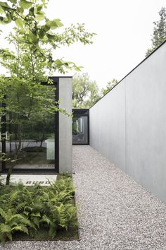 The entrence is hidden between the buro and a large concrete wall. You enter this beautiful home through a large pivot door in aluminium. Thanks to the large glass surfaces you always have a stunning view on the garden. Picture by Annick Vernimmen Minimalist Architecture, Contemporary Architecture, Landscape Architecture, Architecture Design, Modern Entrance, Garden Landscape Design, Facade Design, Modern Landscaping, Facade House