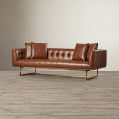 Brown Leather Sofa from Wayfair Canada Tufted sofa with rose gold metal base, perfect for an industrial living room.