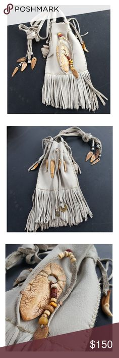 """HP  Gray Fringed Hand Stitched Leather Bag Hand stitched light grey leather medicine bag with cotton lacing.  Double side drawstrings. Decorated with antiqued fossil polymer arrowheads, bone, wood, glass and clay beads, a clay arrowhead, coyote claw.   Perfect for holding sage, cedar, or tobacco for smudging, or a personal medicine bag for your sacred talismans, stones, herbs or mementos. Size: The bag will hold objects up to 4"""" x 4 1/2"""" The bag including the hanging points with fringe is…"""