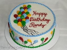 Birthday cake with red, yellow, green and blue balloons.