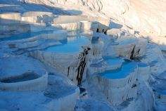 """Pamukkale translated means, literally, """"cotton castle"""", and the name is befitting of this cliff in Aegean. While the cliff faces may look like tremendous glaciers, it is actually rock calcium. You can bathe inside the many mineral-rich pools along the cliff face which are said to help cure illness and disease."""