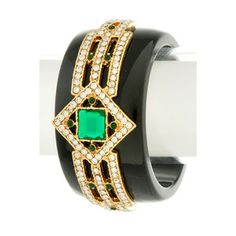 We'vefallenin love with this elegant statement piece! Shiny black resin cuff features intricate gold-tone metalaccentsand inlaid emerald-hue and clear faceted stones. Acrylic base