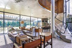 Living moderno en una casa construida en torno a un patio sinuoso. Sillones de cuero y gran ventanal abren el espacio al jardín.