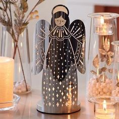 "P91155 Our newest angel radiates a modern shine for an enchanting display the whole year round. Photo-etched metal with glass votive cup to hold a votive or tealight candle, sold separately. 8¾""h, 3½"" base dia. by PartyLite"