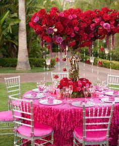 Decoración de rosas rojas y fuscias, con votivas colgantes y guirnaldas de cristal.
