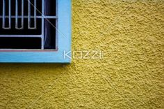 indian window and wall - The corner of a window with a yellow stuccoed wall in Kochi, India.