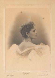 Grã-duquesa Elizabeth Feodorovna em cerca de 1897. Ela é fotografada por trás e está olhando para a direita. Ela está usando um vestido com mangas bufantes e um colar e brincos.