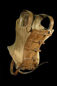 ca 1904 Heavy twill cotton or canvas flying harness in the form of a lady's corset with leather shoulder straps, straps with holes punched to fasten into metal buckles, straps to fasten between the wearer's legs, and inset panels of leather back and front. The back leather panel was originally fitted with a device to hook and unhook the wearer into a flying line.