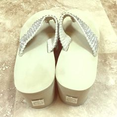 Swarovski Scandalous Flip Flops Worn once! These are super cute, high end sandals! They have clear Swarovski crystals all around the woven strap of the shoe! The wedge is a little over two inches! They are a light beige/neutral color and are super comfy! No trades please. Bought at a boutique in Texas. Scandalous Shoes Sandals