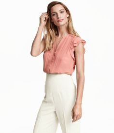 CONSCIOUS. V-neck blouse in chiffon with short ruffled sleeves, pin-tucks and concealed buttons at front, and a gently rounded hem. Made partly from recycled polyester.