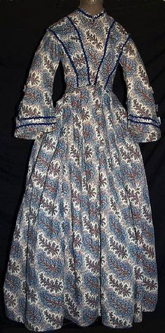 1860's roller printed gown, de-accessioned from Brooklyn Museum. Orange, Red & Blue floral sprays on cream wool challis background. Mostly hand sewn. Piped at waist & armscyes, has original brass hooks with handmade round eyeholes. Bodice fully lined with cream linen and openings are lined with brightly printed calico. Skirt has cartridge pleating, hem edged with blue hem protector, has deep right side pocket, skirt lined with cream & brown polished cotton. (likely 1850s)
