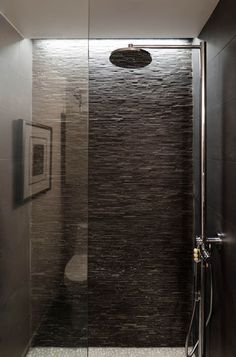 "Faux Skylight: The bathroom doesn't have a natural light source, so Rowell recessed a linear light cove at the back shower wall to create the illusion of a skylight. ""And we wanted the light fixture to wash down the slate and highlight the texture of the wall,"" she says."