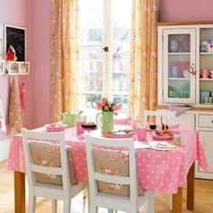 Une salle à manger de couleur rose avec des chaises blanches