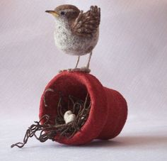 "Beautiful needle felt composition by Jackie Felix of Erie, Pennsylvania. She writes:   ""'Wren Ever' is one of my latest designs; as a bird watcher I am aware it's not technically correct,  but I was so inspired by a little wren who insisted on using a flower pot as a nest last spring  I decided to try and capture not only the experience of her determination, but also the anticipation of the arrival."