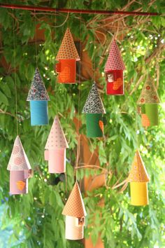 Cute hanging tree houses made from toilet rolls and semi circular pieces of funky card/paper made into a cone roof