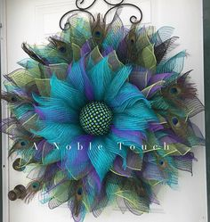 Stunning large peacock wreath by A Noble Touch. This is sure to be a conversation piece. The colors of the deco mesh represent the colors in a peacock feather.Around Large Peacock Wreath, All Year Around Wreath, Large Door Wreath, Large Window Wreath Wreath Crafts, Diy Wreath, Tulle Wreath, Deco Mesh Wreath Tutorial, Wreath Ideas, Peacock Wreath, Peacock Feathers, Peacock Crafts, Purple Peacock