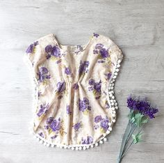 THE SEASIDE BLOOM KAFTAN Introducing our THE SEASIDE BLOOM Kids Beach Kaftan. This gorgeous butterfly kaftan is handmade and adorned with beautiful Pom pom trimmings. Ideal for kids outing, beach or pool cover up as well as resort or holiday wear. Extremely light for packing.