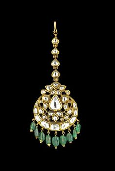 An Indian diamond-set enameled head ornament (Maang Tikka). Set with diamonds, composed of foliate motifs arranged around a central drop form in an open framework, a crescent moon below with an emerald bead fringe, four small drop form diamond-set hinged elements above.