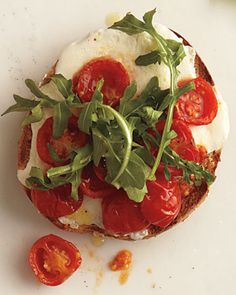Roasted Tomatoes and Mozzarella    1/2 pint (5 oz) cherry tomatoes  2 tsp extra-virgin olive oil  Coarse salt and freshly ground black pepper  1 to 2 slices (1 oz) fresh mozzarella  1/2 whole-wheat bagel   1/2 cup baby arugula