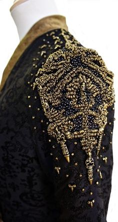 We see Cersei mourning the death of her son, the late King Joffery, in a black brocade gown accented with Lannister gold embroidery. She wears this gown to stand in vigil, with her son Tommen, over. Gold Embroidery, Hand Embroidery Designs, Embroidery Dress, Textiles, Game Of Thrones Dress, Got Costumes, Passementerie, Fantasy Costumes, Fantasy Dress