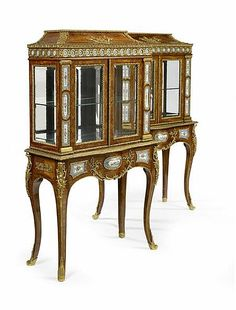 <b>An important pair of Victorian period kingwood, gilt bronze and porcelain mounted display cabinets</b></i> <br /> <br /> in two sections, each pagoda top with a hinged lid enclosing a velvet lined interior, the corners with stiff acanthus leaf mounts and centred by a double scroll mask and dragon mount, each frieze with entwined guilloche incorporating Sevres style porcelain roundels above a pair of rosewood crossbanded and kingwood featherbanded bevelled glazed doors, flanked by ...