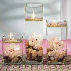 Centerpiece: stones, floating candles, orchids, glass vases