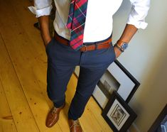 White dress shirt, navy slacks, and plaid tie with brown belt and brown Oxford shoes.