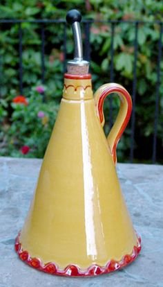 """The unique shape of this French ceramic oil pitcher will make a beautiful French country addition to any kitchen. Made in France.    Size: 10"""" tall, 5.5"""" diameter at base"""