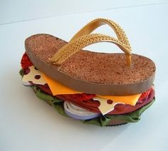 Footwear has turned foodwear with the Brisket Flip Flop... but buyer beware, it's not edible! This fashionable flip flop is made from foam, different fabrics, trims, and crystal rhinestones.