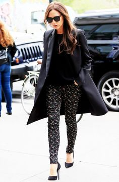 Victoria Beckham wears a Victoria Beckham coat, floral pants, and clutch with a black top and black suede pumps