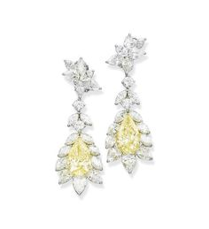 A PAIR OF COLOURED DIAMOND AND DIAMOND EAR PENDANTS Each set with a pear-shaped light yellow diamond, weighing 5.22 and 5.02 carats, within a marquise, pear and brilliant-cut diamond foliate surround, to the marquise and pear-shaped diamond cluster top, mounted in platinum and 18k gold