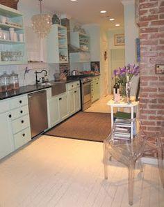 Love this Galveston cottage kitchen--chandelier, exposed brick, open shelving.