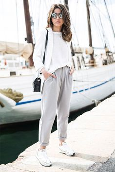 Street Style - The Top Blogger Looks Of The Week: Fashion Blogger 'Lovely Pepa' wearing a white blazer, a white light sweater, grey joggers, white sneakers, mirror sunglasses and a black shoulder bag. Spring outfit, sneakers outfit, casual outfit, comfy outfit, athleisure outfit.