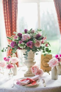 wedding centerpieces, i like the urn in the middle of the table but somethings off on this for me either theres not enought of the color flowers  that are singular on the table in the centerpiece and i love the greenery but it almost looks plastic. maybe it just needs votives.