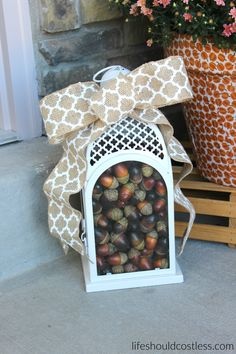 Fall lantern filled with acorns. Burlap bow. Rustic/Farmhouse decor idea. See this and many other popular decor pins at lifeshouldcostless.com.