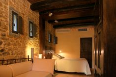 Deluxe Family Room Le Feritoie - stone walls and wooden beams on the ceiling. 1st floor, accessible from the outdoor or by elevator from the interiors of the castle.
