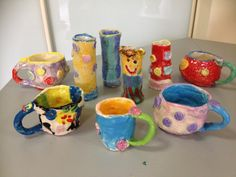 Kids Pottery Coil mugs and slab vases, decorated with underglazes and clear glaze fired.